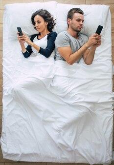 美しい女性とハンサムな若い男性の上面写真は、大きな白いベッドに横たわっている間、スマートフォンを使用しています。オンラインチャット。カップルの上の写真。