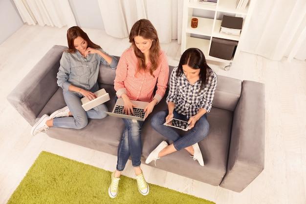 Фотография трех девушек, работающих на ноутбуках и планшетах, вид сверху