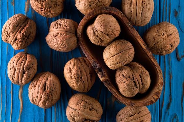 Фото вида сверху целых грецких орехов на покрашенном синем деревянном столе.