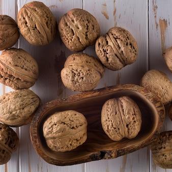 Фото вида сверху целых грецких орехов на окрашенном белом деревянном столе в шаре.
