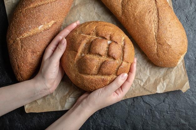 ライ麦パンを持っている女性の上面写真。