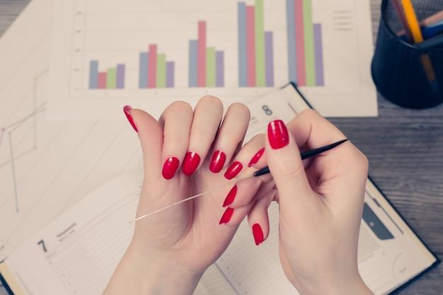 爪を持っている女性の手の上面写真は、開いた日記と背景のグラフに対して失敗します