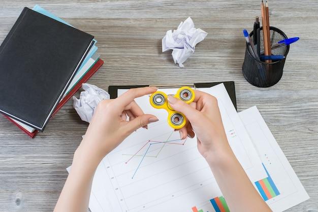 Фото вида сверху женских рук, играющих с прядильщиком непоседы во время перерыва на работе. популярная и горячая игрушка.