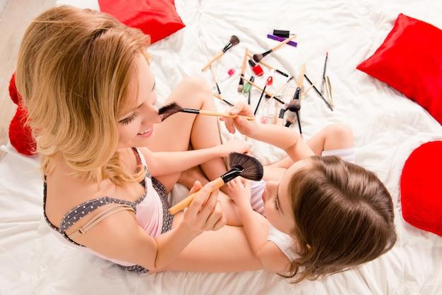 化粧をしている若い女性と彼女の小さな子供の上面写真