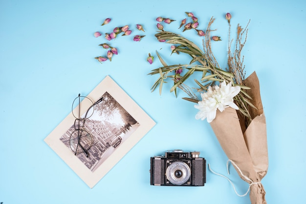 Top view of photo  old camera with white color chrysanthemum flower in craft paper and dry rose buds scattered on blue