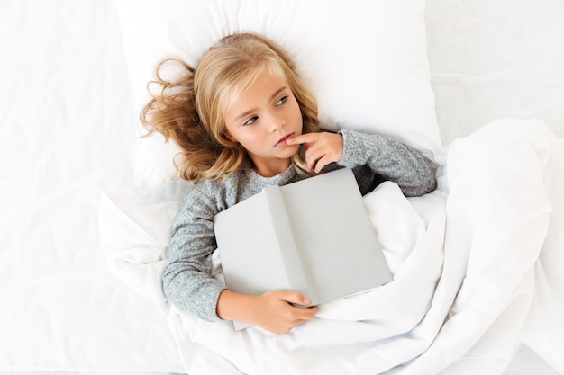 Top view photo of thoughtful little girl lying in bed with gray book, looking aside