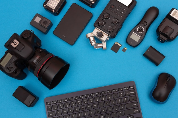 Top view of photographers videographers or video bloggers workplace digital gadgets lying on blue ta...