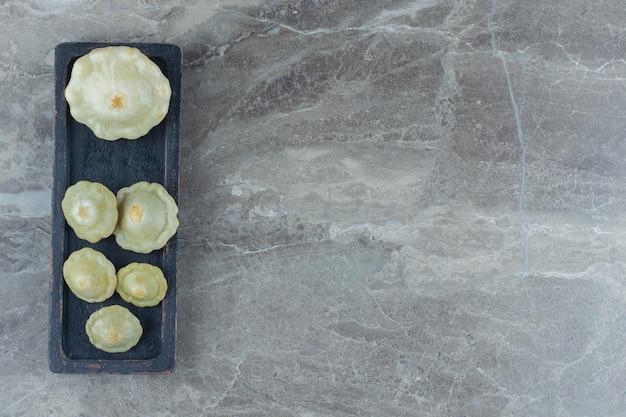 Vista dall'alto del sottaceto zucca verde in padella su tavola di legno nera.