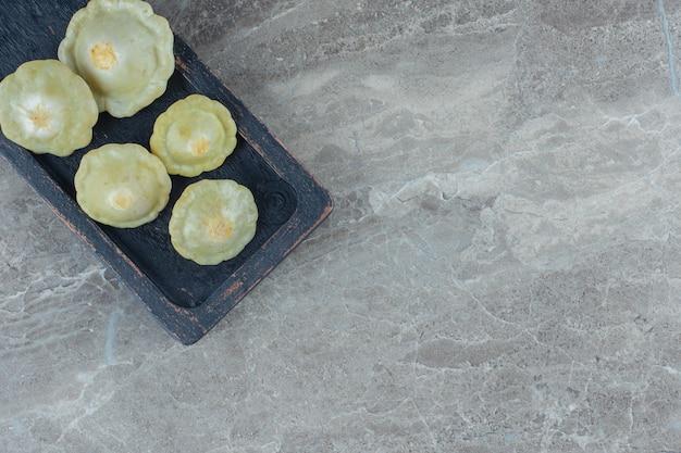 Vista dall'alto del sottaceto zucca verde in padella su tavola di legno.