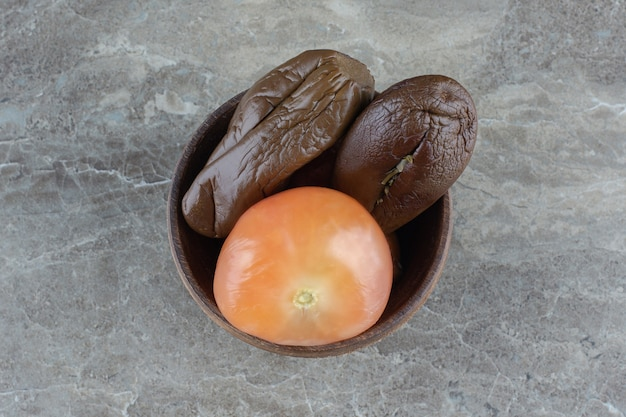 Top view of pickled eggplant and tomato in wooden bowl.