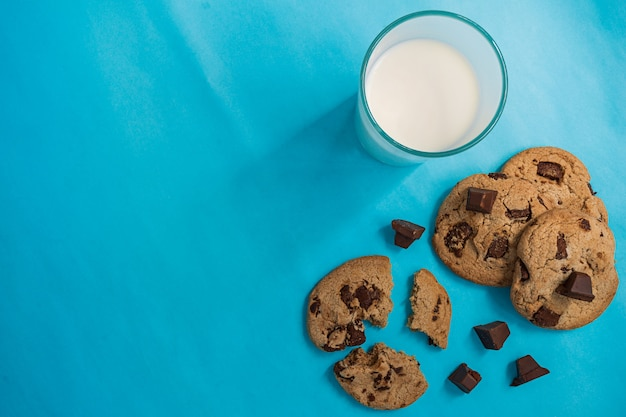 Top view  picture of chocolate cookies and a cup of milk on blue background