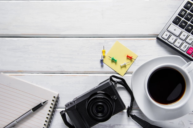 Top view picture of coffee, camera and notebook on white wood background