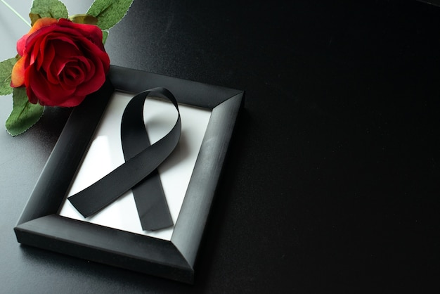 Top view of picture frame with black bow on dark wall