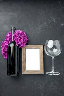 커플 선물 색상 결혼을 느끼는 어두운 배경에 와인 한 병과 꽃이 있는 상위 뷰 사진 프레임