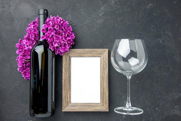 Фоторамка с бутылкой вина и цветами на темном фоне, вид сверху, любовь, чувство, пара, подарок, цвет, брак.
