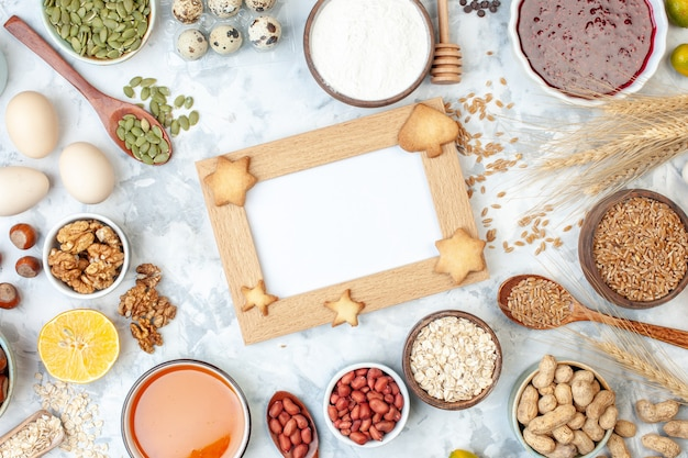 Top view picture frame with jelly eggs different nuts and seeds on a white dough color cake sweet photo sugar pie nut heart