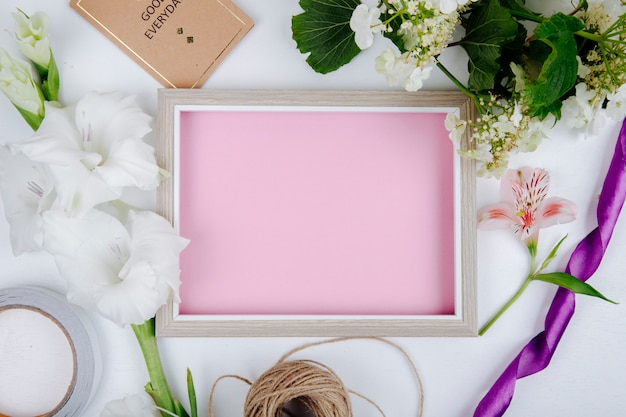 Top view of a picture frame with pink sheet of paper small postcard rope and white color gladiolus flower and a branch of blooming viburnum on white background