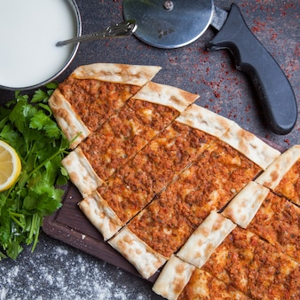 Top view pide with minced meat and ayran and pizza knife in cutting board