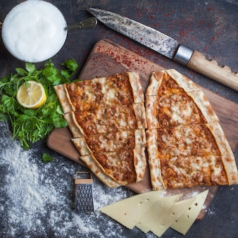 Top view pide with minced meat and cheese and ayran and knife in cutting board