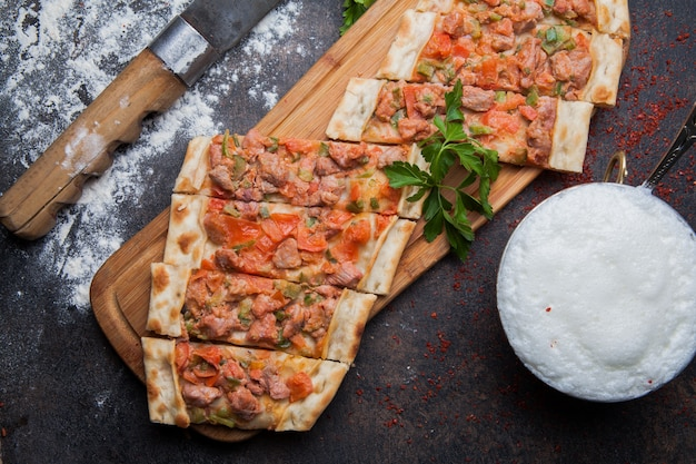 Top view pide with pieces of meat and knife and ayran in cutting board