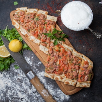 Top view pide with pieces of meat and parsley and lemon and knife and ayran in cutting board