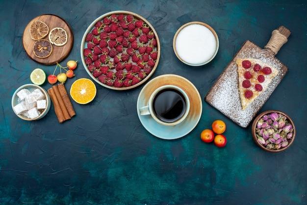 Вид сверху кусок торта запеченная конфета с малиной и чаем на темно-синем столе ягодный сахарный торт пирог запекать бисквит