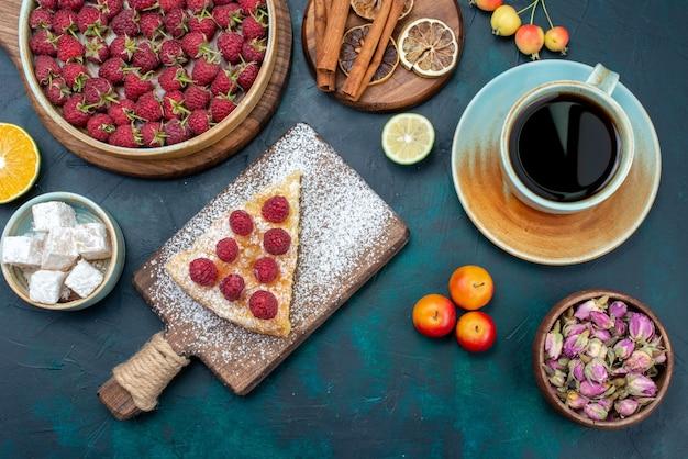 Вид сверху кусок торта, запеченного сладкого с малиной и чаем на темном столе, ягодный пирог, бисквит