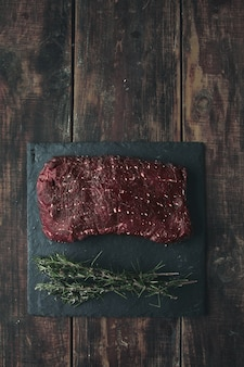 Вид сверху кусок сырого мяса на черной каменной подушке с розмарином, все на состаренном деревянном столе