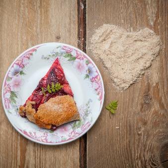 Вид сверху кусочек клубничного пирога с ореховыми крошками и сердечком в круглой цветочной тарелке