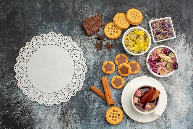 Vista dall'alto di un pezzo di pizzo bianco con tisane e biscotti e fiori secchi su fondo grigio
