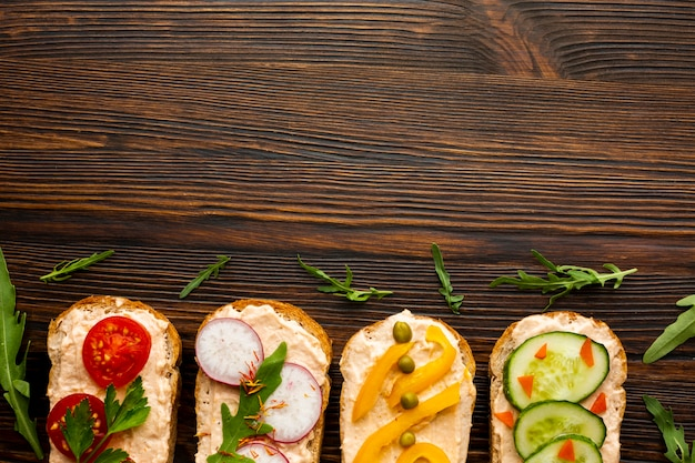 Top view pieces of bread with veggies with copy space