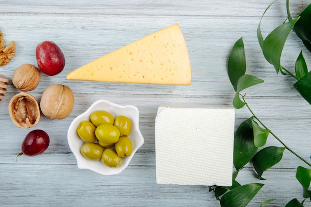 Top view of pieces of cheese with fresh grape, pickled olives and walnuts on grey wooden table