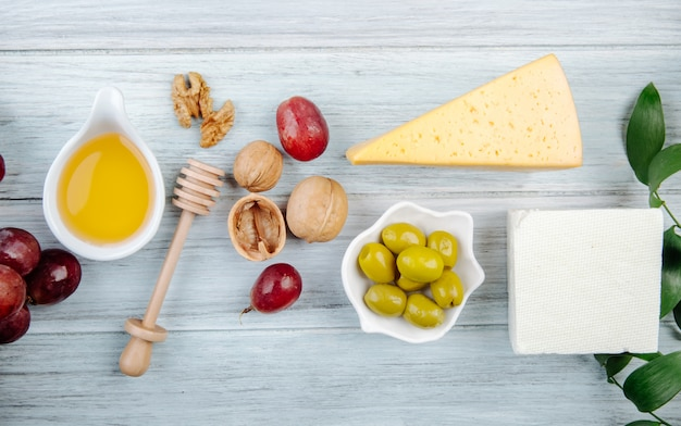 Top view of pieces of cheese with honey, fresh grape, pickled olives and walnuts on grey wooden table