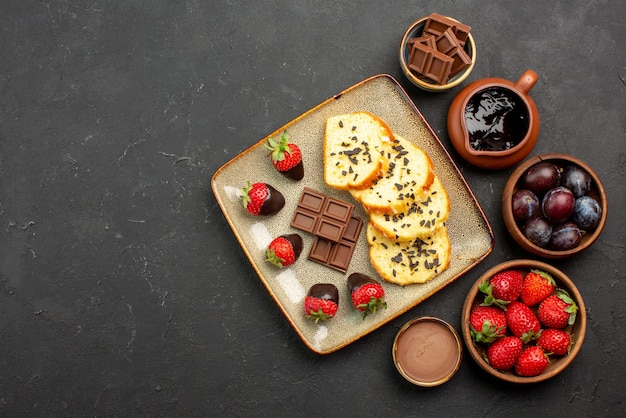 テーブルの右側にチョコレートとイチゴのケーキとイチゴのベリーとチョコレートソースのボウルを食欲をそそるケーキの上面図