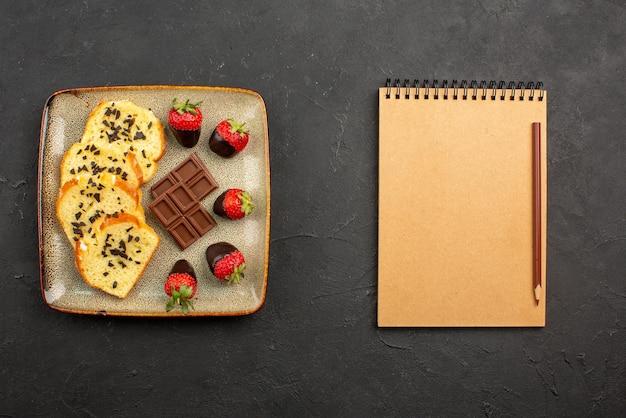 어두운 테이블에 갈색 연필이 있는 노트북 옆에 초콜릿과 딸기가 있는 식욕을 돋우는 케이크 조각