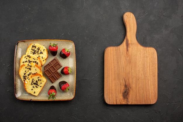 暗いテーブルの上の木製のまな板の横にチョコレートとイチゴとケーキの食欲をそそるケーキの上面図
