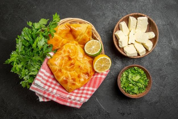 上面図パイとハーブ木製バスケットとハーブとチーズのボウルの市松模様のテーブルクロスの横にある2つのパイレモンとハーブ