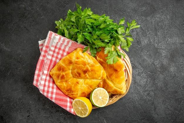 上面図パイとハーブ木製バスケットの市松模様のテーブルクロスの横にある2つのパイレモンとハーブ