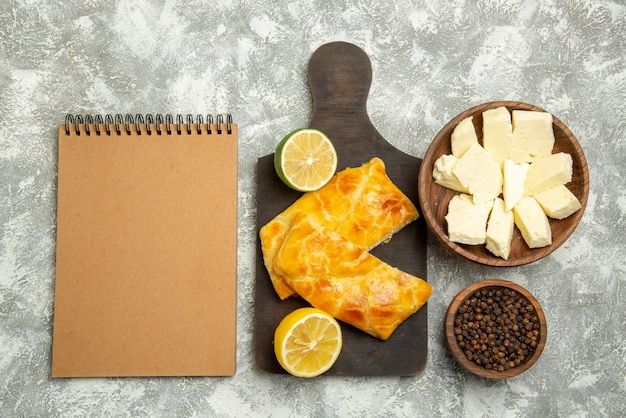 Top view pies cheese cream notebook next to the bowls of black pepper cheese appetizing pies and lemon on the cutting board on the right side of the table