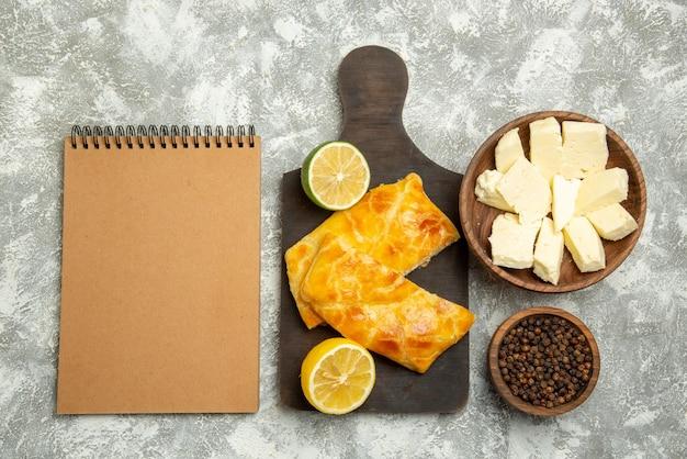 검은 후추 치즈 그릇 옆에 있는 상위 뷰 파이 치즈 크림 공책 테이블 오른쪽에 있는 커팅 보드에 식욕을 돋우는 파이와 레몬