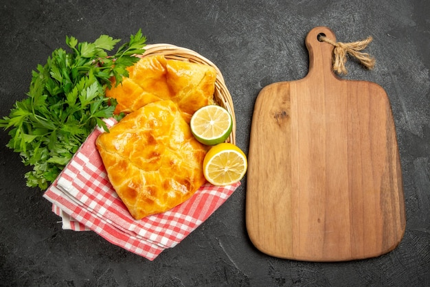 Top view pies and herbs wooden cutting board next to two pies lemon and herbs next to the checkered tablecloth in the wooden basket