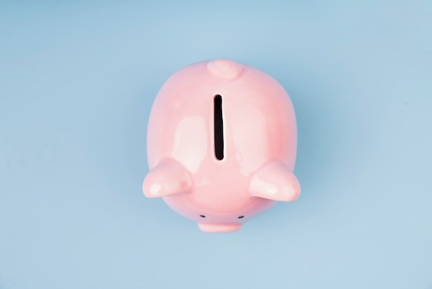 Top view piggy bank on blue wallpaper