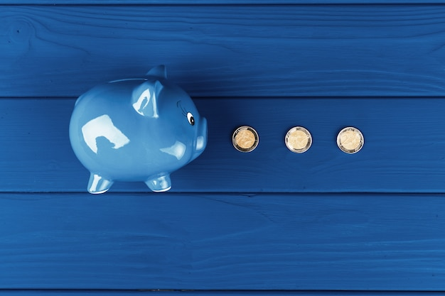 Top view of a piggy bank on blue