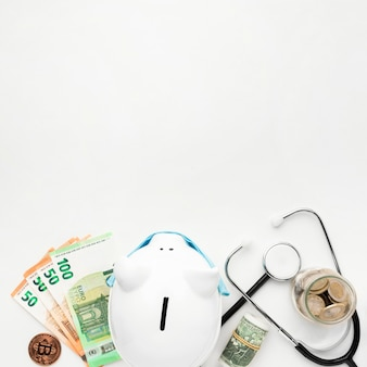 Top view piggy bank with money and stethoscope