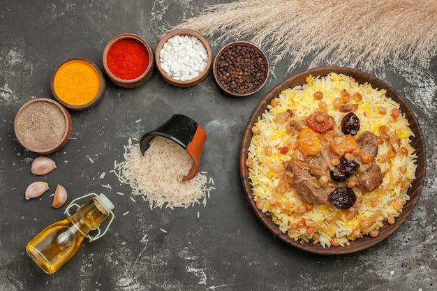 쌀의 기름 그릇의 상위 뷰 필라프 필라프 숟가락 향신료 마늘 병 다섯 그릇