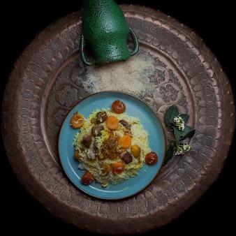Вид сверху плов с мясом и сушеными фруктами и каштаном и кувшином в круглой тарелке