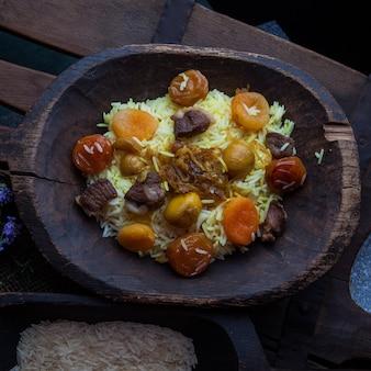 Вид сверху плов с мясом и сушеными фруктами и листьями каштана и риса и розмарина в деревянной тарелке