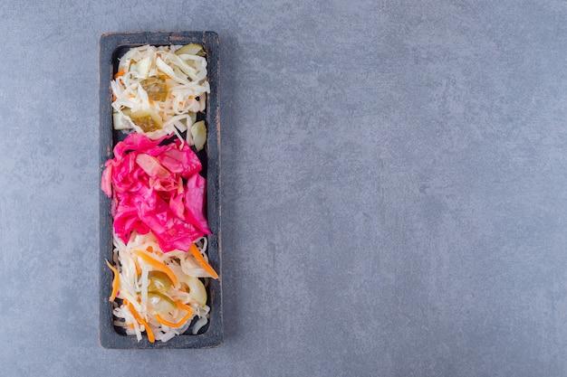 Vista dall'alto del mucchio di cavoli in scatola. tre tipi di crauti sul piatto di legno.