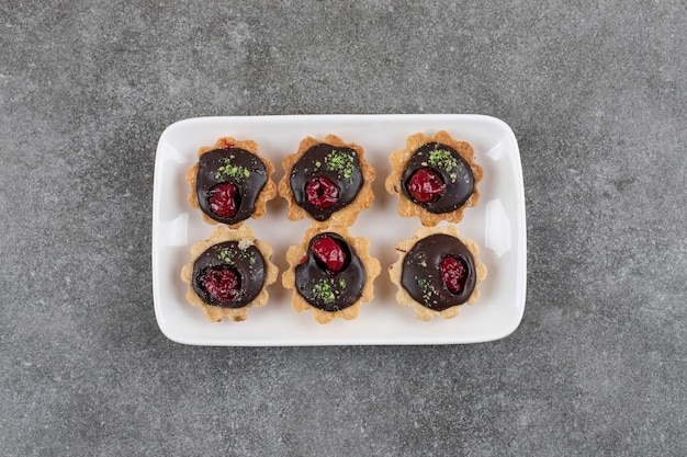 Vista dall'alto. mucchio di biscotto al cioccolato sul piatto bianco sopra il tavolo grigio.