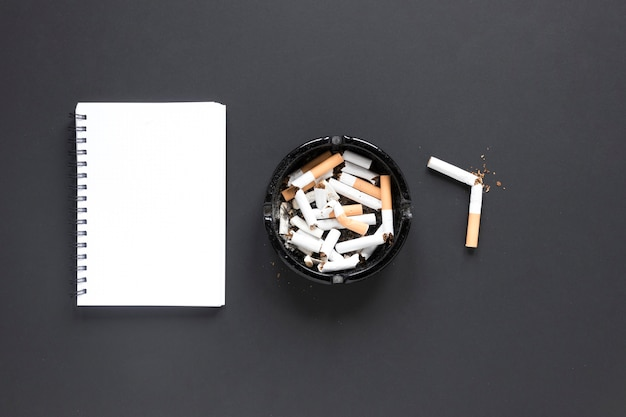 Top view pile of cigarettes with notebook